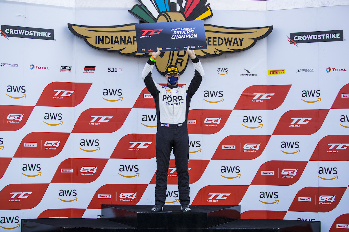 James Clay holding Driver's Champion sign at Indy