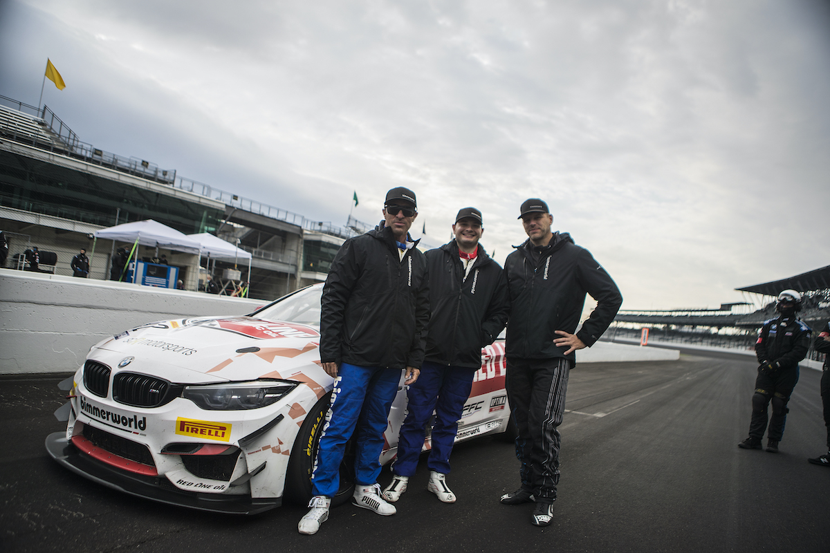 Clay, Auberlen, Walker, Jr. in front of the Red Line Oil M4 GT4 at Indy