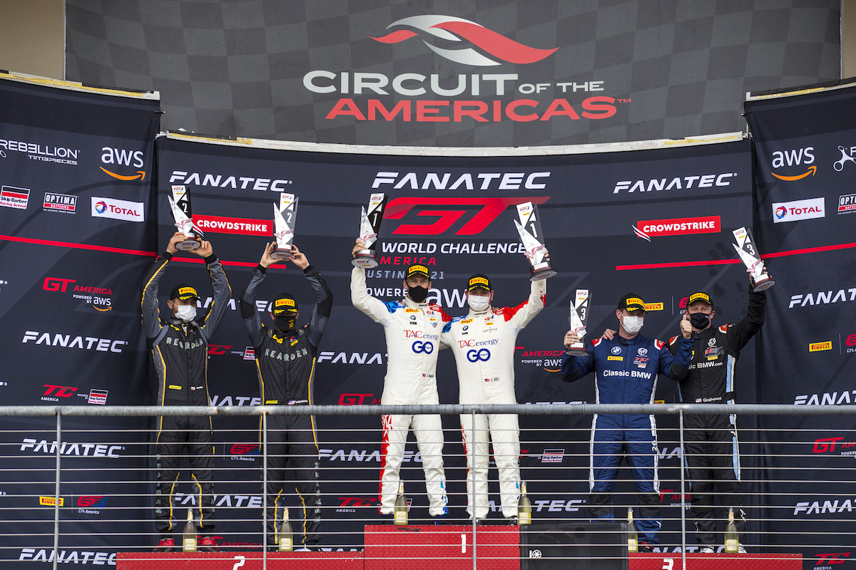 BimmerWorld drivers Chandler Hull and Jon Miller celebrating their win on the top step of the podium at COTA